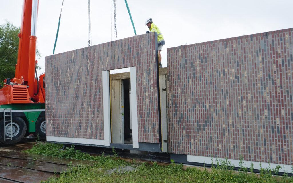 Manipulatie van prefab betonwand met bakstenen